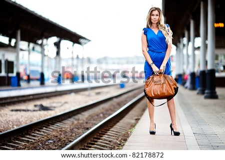attractive lady waiting train on the platform of railway station