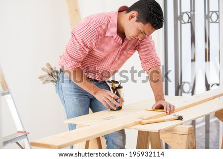 Attractive Latin contractor using a tape measure before cutting a wood board at work