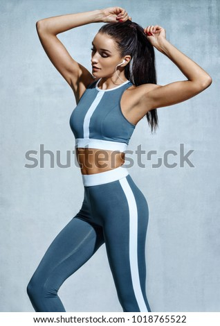 Attractive latin woman in fashionable sportswear on grey background. Strength and motivation