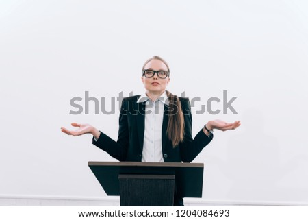 attractive lecturer standing at podium tribune and showing shrug gesture during seminar in conference hall
