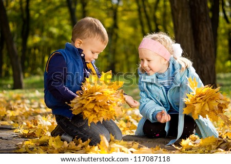 Attractive little brother and sister in autumn woodland kneeling amongst colourful yellow fallen leaves watching an insect on the boys arm with fascination