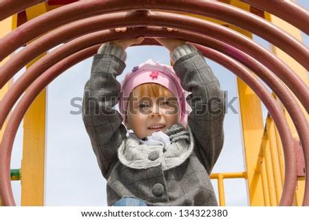 Attractive little girl on outdoor playground equipment