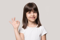 Attractive little 6 years old smiling cutie showing okay gesture. Close up head shot portrait happy girl accepting idea, isolated on grey studio background. Agreement, approval, confirm, ok concept.