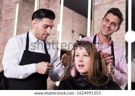 Attractive long-haired brunette getting haircutting from two professional hairstylists in salon