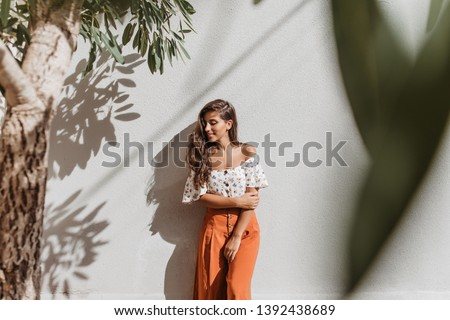 Attractive long-haired brunette woman in stylish culottes and white top posing against white wall and olive tree #1392438689