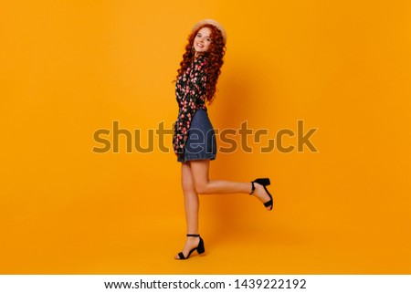 Attractive long-haired redhead lady in miniskirt made of denim, beautiful blouse and boater is coquettishly raising her leg against orange background #1439222192