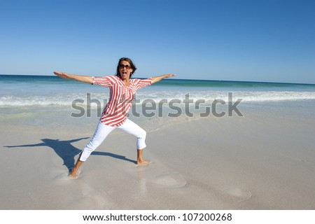 Attractive looking mature woman, happy doing exercises at beach, isolated with ocean and blue sky as background and copy space.