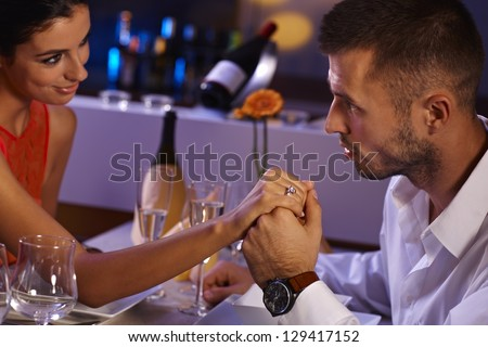 Attractive loving couple holding hands at dinner table, looking affectionate.