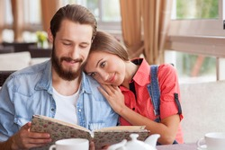 Attractive loving couple is dating in cafe.  They are sitting at the table and embracing. The bearded guy is holding a menu. The pair is choosing food and smiling