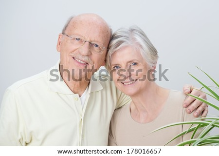 Attractive loving senior couple standing arm in arm with their heads touching enjoying a tender moment together and smiling at the camera