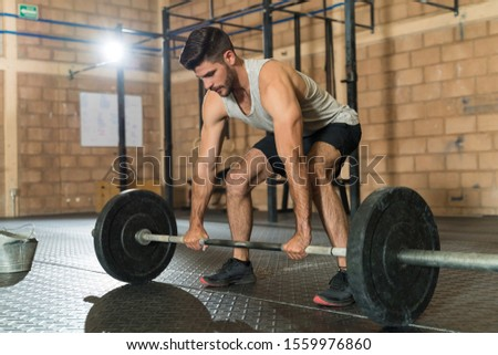 Attractive male athlete gripping barbell before lifting during cross training at health club