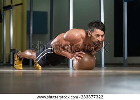 Attractive Male Athlete Performing Push-Ups On Medicine ...