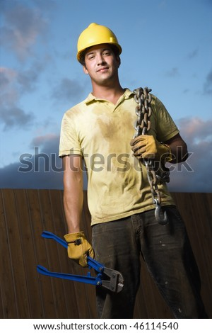 Attractive male construction worker in a yellow hardhat smiles into the camera. He holds a heavy chain on his shoulder and bolt cutters in his hand. Vertical shot.