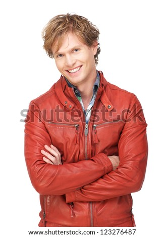Attractive male fashion model wearing a red leather jacket looking at camera and with a smile expression on his face. Isolated on white background