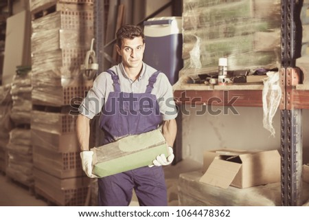 attractive male in uniform is choosing cement in the building store room