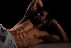Attractive male model lying and posing on bench