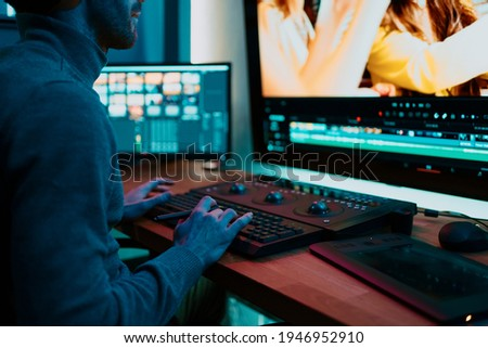 Attractive Male Video Editor Works with Footage or Video on His Personal Computer, he Works in Creative Office Studio or home. Neon lights Photo stock ©