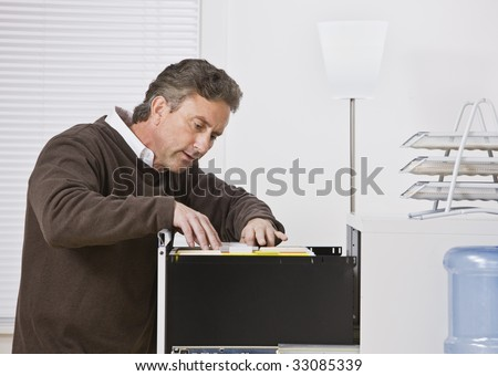 Attractive male wearing a sweater in office, looking for file in filing cabinet. Looking away from camera. Horizontal. - stock photo