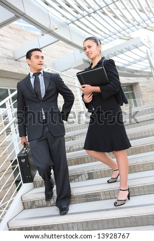 Attractive man and woman business team on stairs at office building