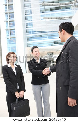 Attractive man and woman business team shaking hands at company