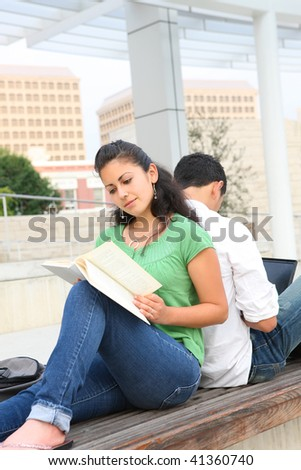 Attractive man and woman students at college studying reading a book