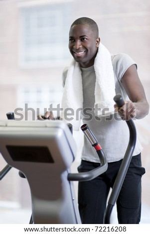 Attractive man at health club, exercising on stepper