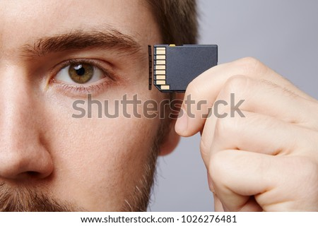 Attractive man at studio background, business concept, copy space, portrait, holding memory card, close up.