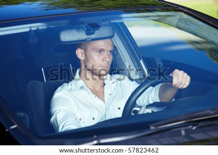 Attractive man behind the wheel of his car