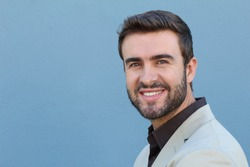 Attractive man face portrait with a white perfect smile isolated on a blue background