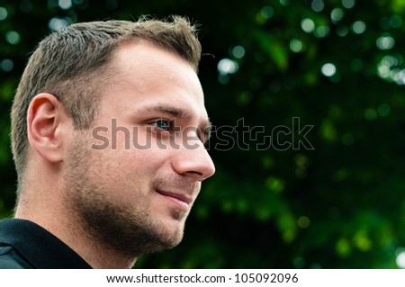 Attractive man head profile with green tree on background