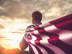Attractive man holding Flag of the United States on blue sky background on a clear, sunny day. View from the back, close-up. National holiday concept