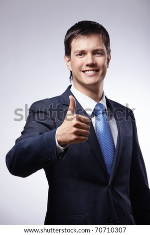 Attractive man in a suit with a thumb up on a gray background
