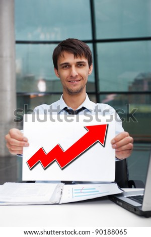 Attractive man in business suit with sign of up graph sitting at his office and smiling to camera