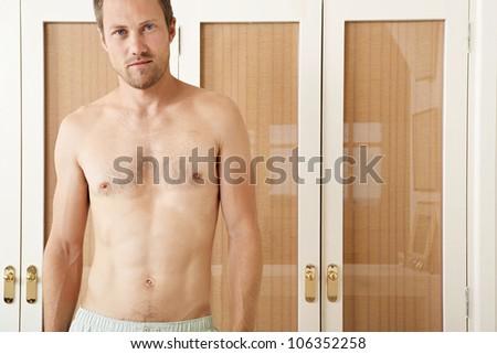 Attractive man in front of wardrobe doors in a bedroom in underwear, smiling.