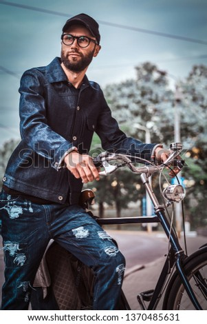 Attractive man in glases, denim and cap is standing on the street. He is holding his bicycle. He is looking away. Trees and sky at the background. #1370485631