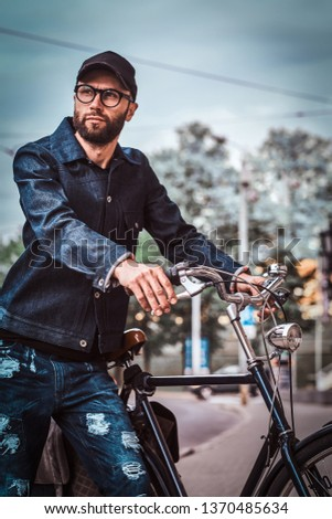 Attractive man in glases, denim and cap is standing on the street. He is holding his bicycle. He is looking away. Trees and sky at the background. #1370485634