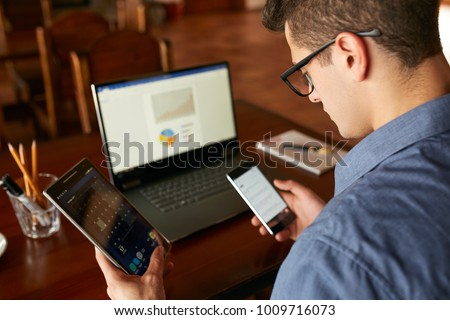 Attractive man in glasses working with multiple electronic internet devices. Freelancer businessman has laptop and smartphone in hands and laptop on table with charts on screen. Multitasking theme.