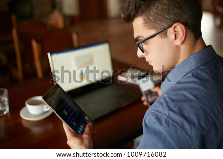 Attractive man in glasses working with multiple electronic internet devices. Freelancer businessman has laptop and smartphone in hands and laptop on table with charts on screen. Multitasking theme. - Shutterstock ID 1009716082