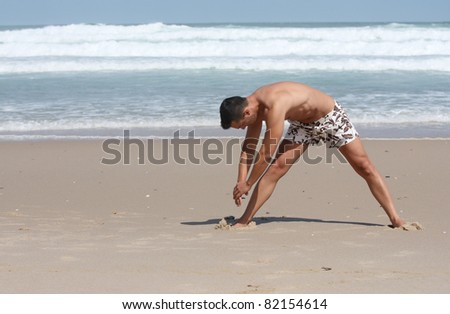 attractive man making stretching movements before run on the beach