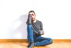 attractive man on his 40s dressing casual sitting on the wooden floor of an apartment with gesture of tiredness or concern with white wall as background