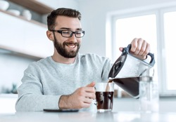 attractive man pouring himself a Cup of morning coffee
