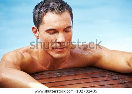 Attractive man relaxing in swimming pool with blue water