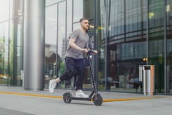 Attractive man riding a kick scooter at cityscape background.
