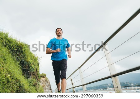 Attractive man running on a wooden walkway next to the sea. Daily training. Stock photo ©