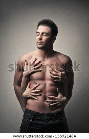 attractive man shirtless with women's hands on the torso