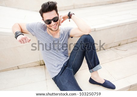 attractive man smiling - dressed casual posing outdoors