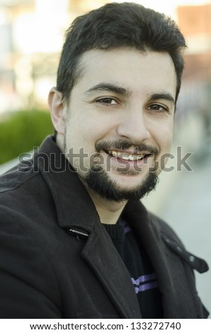 Attractive man smiling outdoors. Appearance Latin or Arabic.