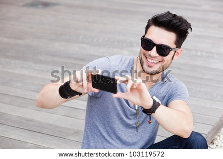attractive man taking photos with a black smartphone
