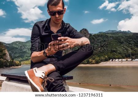 Attractive man using smartphone, stylish guy, black wear, hand watch, pretty, attractive, tan, man in sunglasses, black shirt, casual, fashion #1237196311