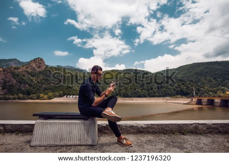 Attractive man using smartphone, stylish guy, black wear, hand watch, pretty, attractive, tan, man in sunglasses, black shirt, casual, fashion #1237196320